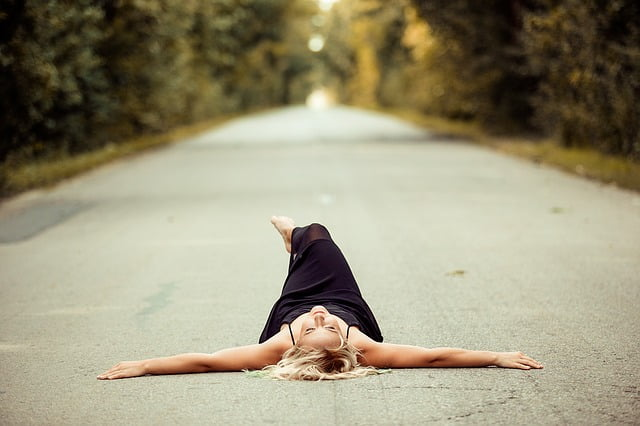 Lady exercising on the ground, stretched hands and one leg on the other.